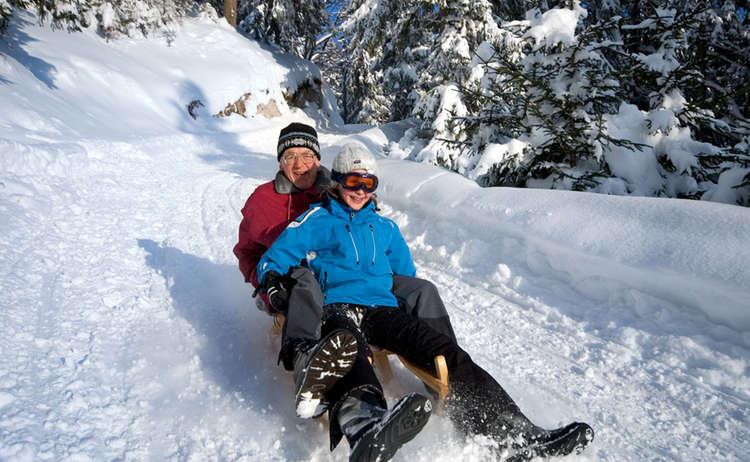 Opa und Enkel beim Schlittenfahren